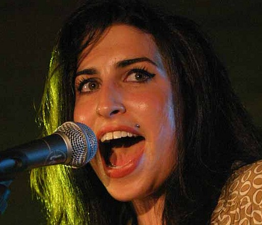 Amy Winehouse performs in concert. One of her former bodyguards 'tried to kill a man in his home'