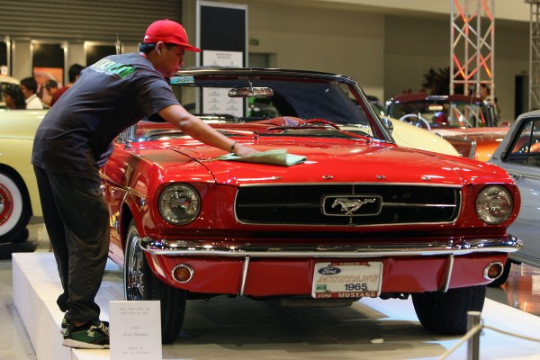 A worker waxes a vintage 1965 Ford Mustang during the Grand 3-Ring Motoring Event in Pasay City, the Philippines