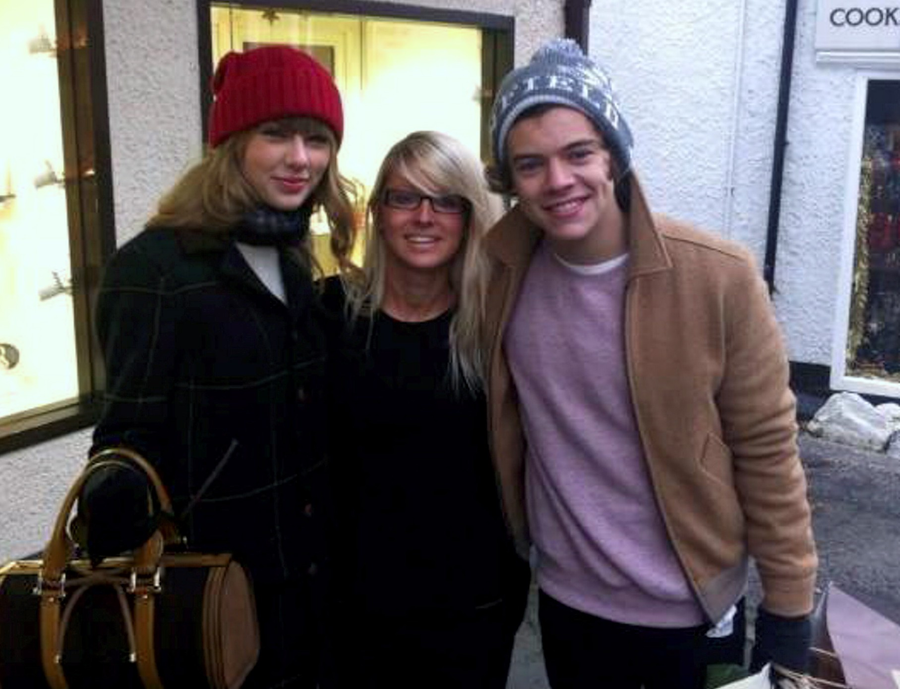 Harry Styles and Taylor Swift pose for a photo with a fan during a shopping trip to the Lake District