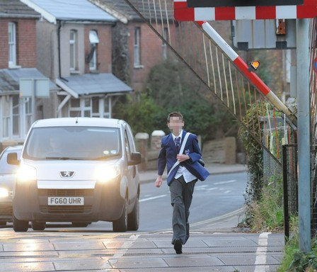 The foolhardy schoolboy jogs over the level crossing as the barriers come down