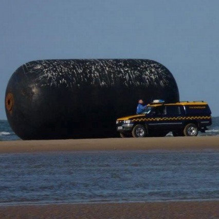 Tourists flocking to the Norfolk coast were stunned when they saw a giant buoy the size of a BUS washed up on the shore