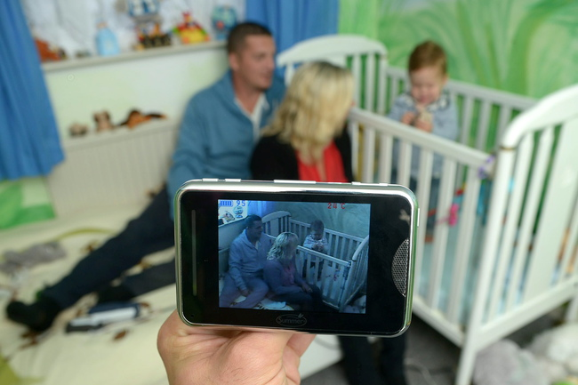 Ollie Johnson in his cot with mother Sarah, 32, and father Stephen, 28, who monitor him using CCTV
