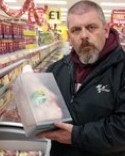 Annoyed shopper Simon Wightman holds one of the pieces of meat from Iceland which is locked in the security case after a spate of thefts