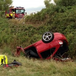 Fire crews next to the upturned car in which Mark Beckford survived for 14 hours