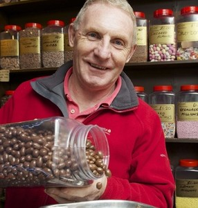 John pours chocolate coated nuts. He used his police pension to open the shop