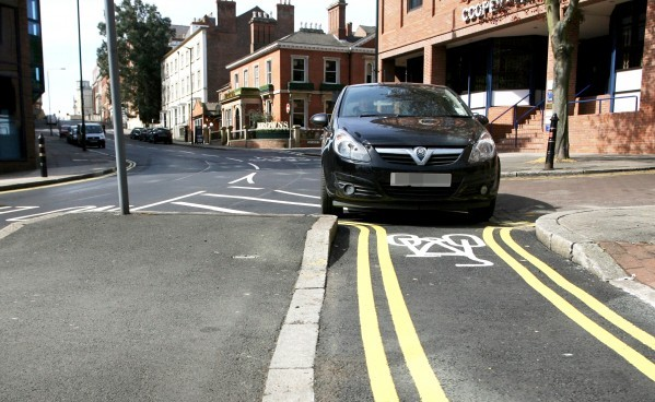 Double yellow lines painted on a cycle track in Nottingham that's too narrow for cars to even drive down