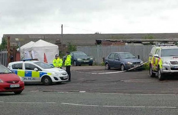 Police attend the scene of where the body of a man was discovered in a burnt out car near to Cradley Heath railway station on Saturday night