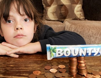 Paige with the 60p collection of pennies from her piggy bank and a Bounty bar like the one she wanted to buy