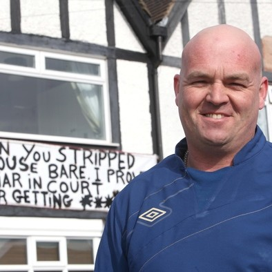 Lorry driver Robin Baker with the homemade sign he put up outside his house to show his wife-of-22-years Jeanette Baker, 47, that she couldn't walk all over him in their divorce proceedings
