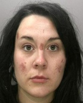 Raven-haired 'femme fatale' Emily Goode with scratches on her face in the police mugshot