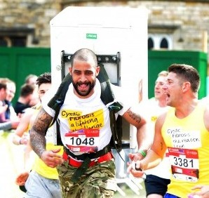Lance Corporal Iain Maynard, 27, runs a six mile course with a fridge strapped to his back