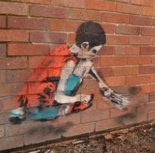 A resident in Lichfield admirers the graffiti which is believed to be that of the renowned artist Banksy