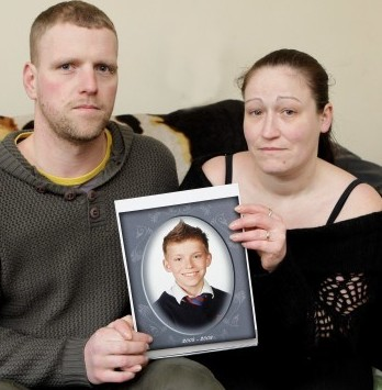 Joshua's devastated mother Michelle and stepdad Philip Downes hold a picture of him