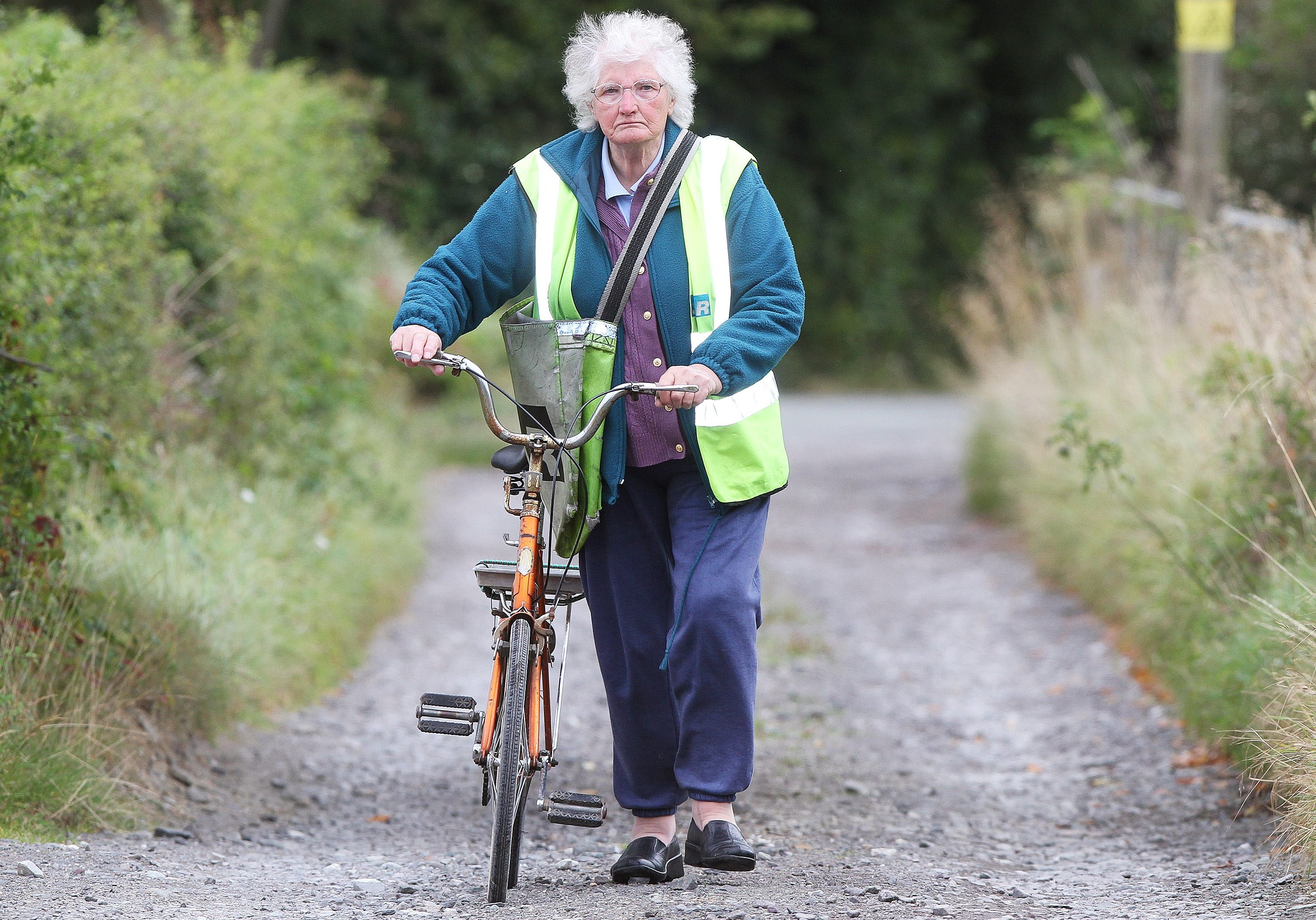 Joyce pushes her trusty bike along a country road. She loves the exercise and fresh air when she's on her round
