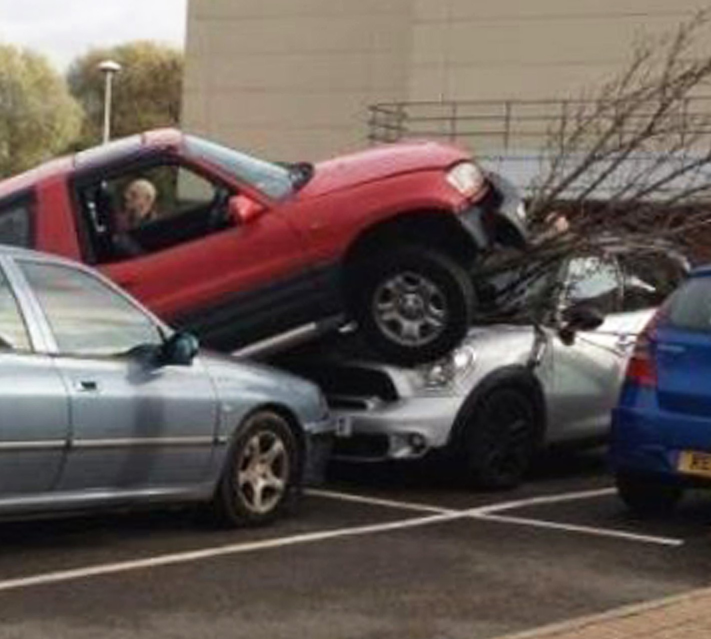 The middle-aged motorist crushes a car and a tree as he tries to park his jeep at a retail park