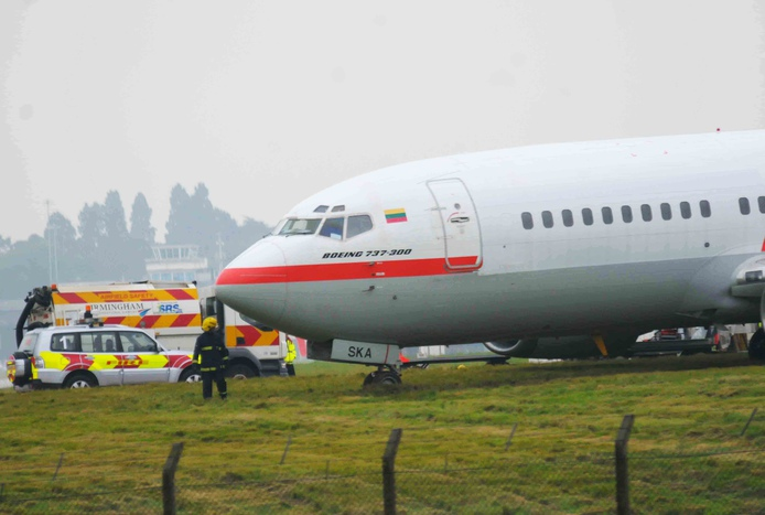 The Boeing 737 peers over a grassy bank after skidding off the runway at Birmingham Airport this afternoon