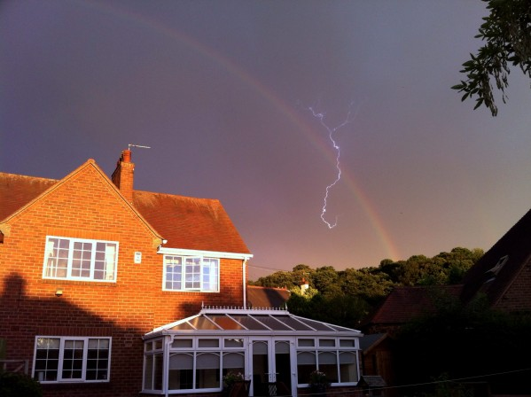 This is the spectacular moment a photographer struck gold by capturing a bolt of lightning cracking through a rainbow during a freak weather display