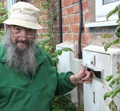 Pensioner Mike Stevens next to the letter box surrounded by raspberry bushes which postmen claim are 'aggressive' and a health hazard