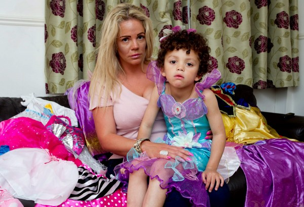 Romeo Clarke, 5, sitting with his mother Georgina Clarke amongst all the dresses he owns