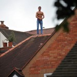Muscle man: The fugitive perches on top of the roof after trying to escape cops