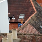 Hands up: The man sits hopelessly on top of the roof after being cornered