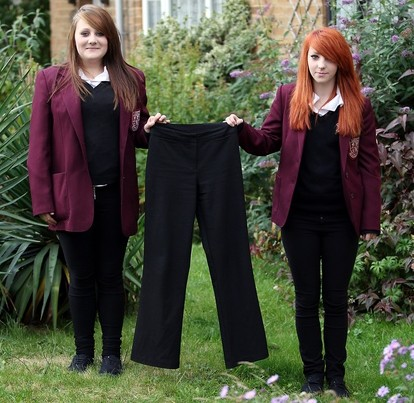 """Erin Jacobs, left, and Tammi Allen, right, hold their """"skinny fit"""" trouser that they were put in 'isolation' for"""