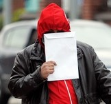 Usman Yasin, 30, covers his face as he arrives at Burton magistrates court