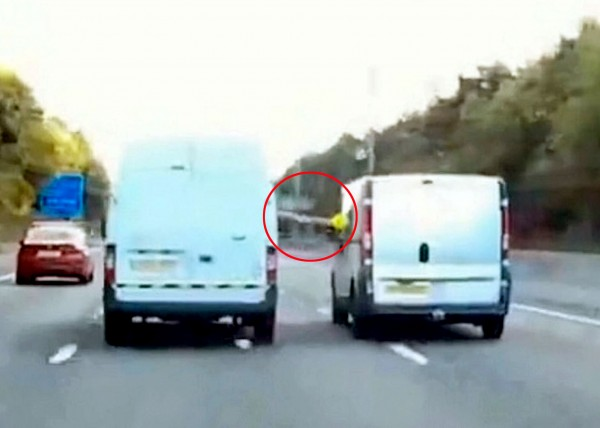 This is the terrifying moment that two vans nearly collide in the fast lane of a Midland motorway after a driver reaches out and grabs a DRINK from a second van at nearly 60mph