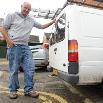 Andrew Wilson stands next to his van on his own driveway in the same position it was parked when he was given a ticket