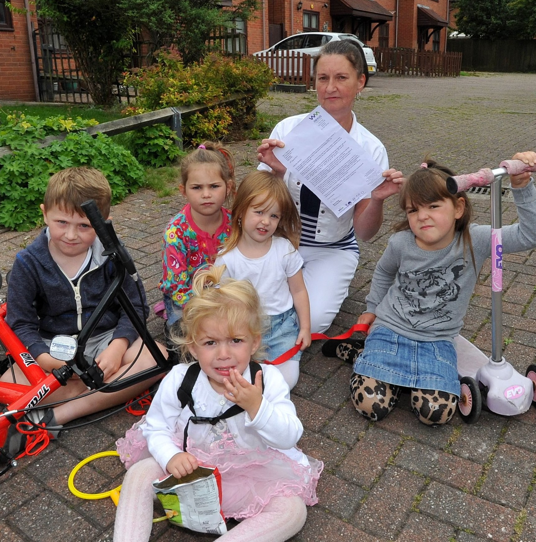Carol Stanford from Wensleydale Drive, Blackpole, Worcester, with some of the children who play on the parking area next to her house