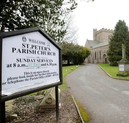 St Peters parish church in Bromyard, Herefordshire, where Robert Marsh slipped on berries from trees (pictured left next to the church) and then sued the council for £33,000