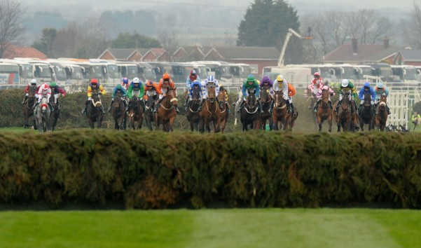 The horses thunder towards a jump at the Grand National