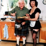 Savile smirks alongside a waitress in a maid's costume on the day that the Prince of Wales visited him at his cottage in Glencoe in July 1999