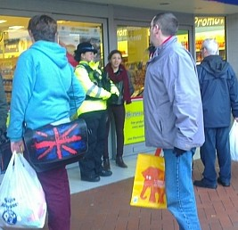 A police officer stands at the entrance to the 99p store in Wrexham, North Wales, after a mad dash for bargains in a half price sale caused chaos