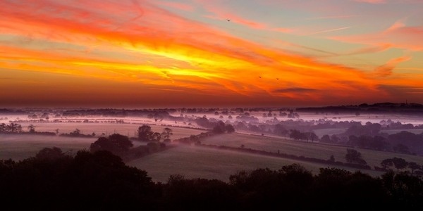 Mist rises over fields in Wells, Somerset, during a beautiful morning sunrise