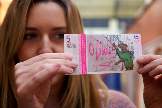 A local shopper inspects a Bristol five pound note, which is intended to stimulate the local economy