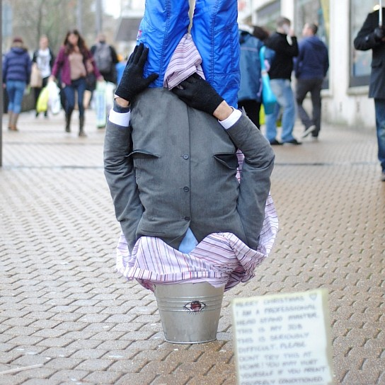The street performer standing in his head in a bucket