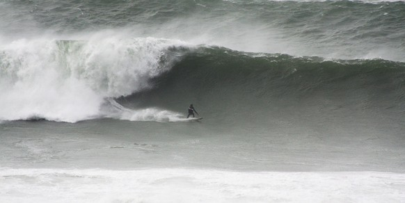 The surfer makes light work of the wave as he carves it up
