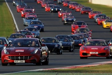 The convoy of sports cars go round a bend. They have a staggering amount of combined engine power
