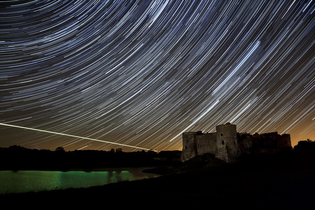 This star trail photograph was created by 'stacking' dozens of seperate exposures including the one frame with the burning fireball