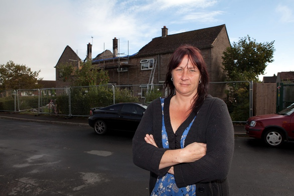 Belinda Standbridge, 45, stands outside her fire damaged house (far right) after builders were called in to fix a gutter