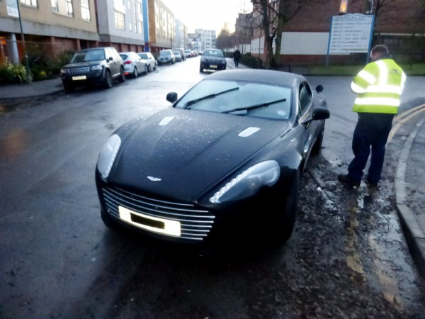 A police officer next to the Aston Martin after it was flooded