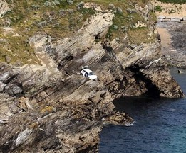 Emergency services attend the scene where a motorist has died after their car went off a cliff