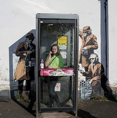 A woman poses inside the phone box next to the mural depicting spies listening in on her call