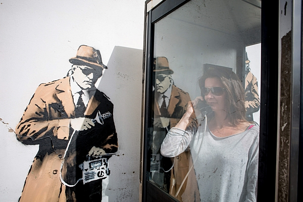 A woman poses inside the phone box