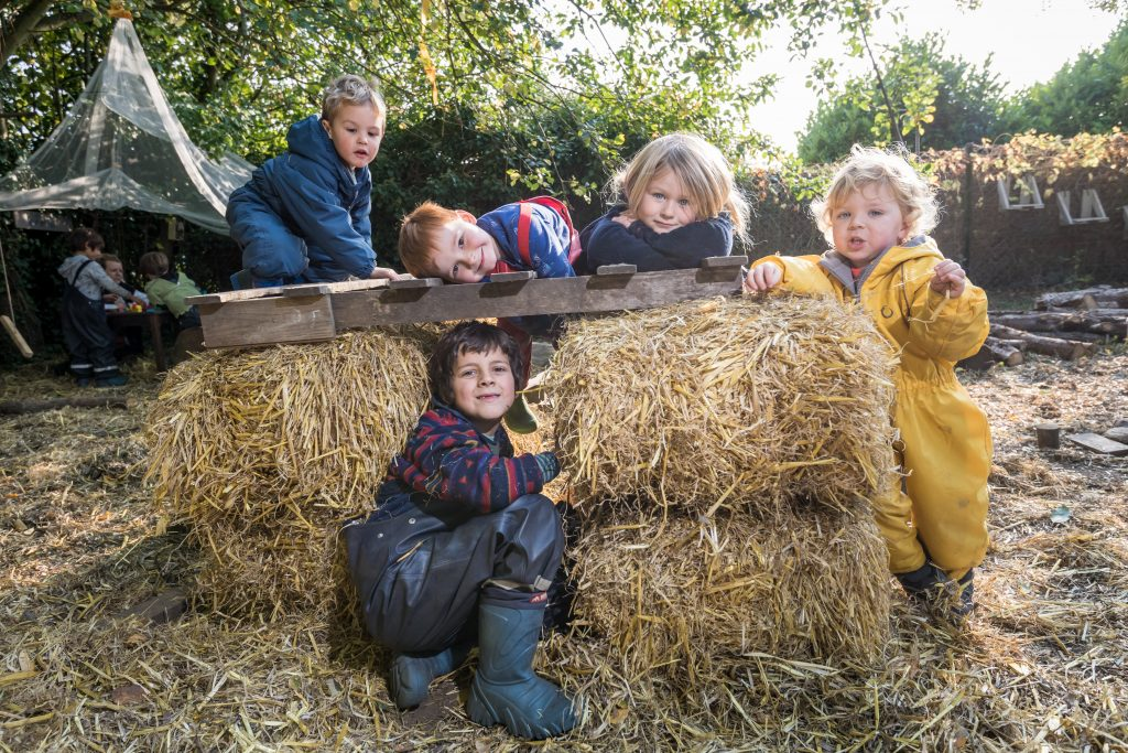 Children play on bales of straw at the Dandelion day nursery in Marsham, Norfolk where the children are educated outside and don't play with conventional toys but build their own.