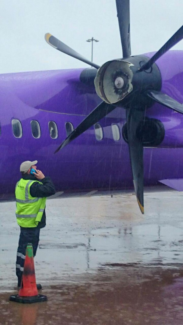 An airport worker inspects the damaged propeller after the plane landed at Birmingham