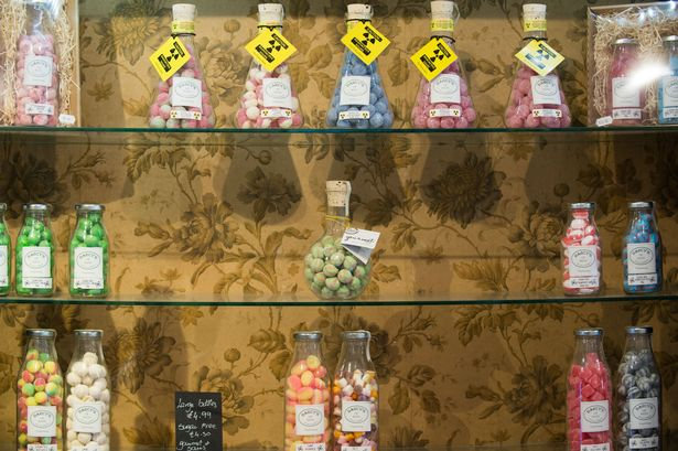 Sweets sold on shelves in front of 19th Century Victorian wallpaper.