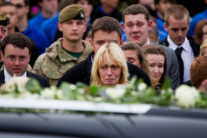 The pain and grief is evident on the face of one woman as the Union Jack covered coffins pass by