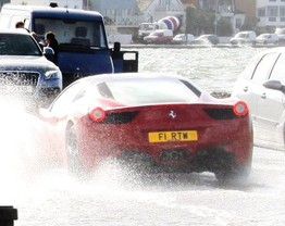 A Ferrari battles through the flood water that threatened Sandbanks, Dorset